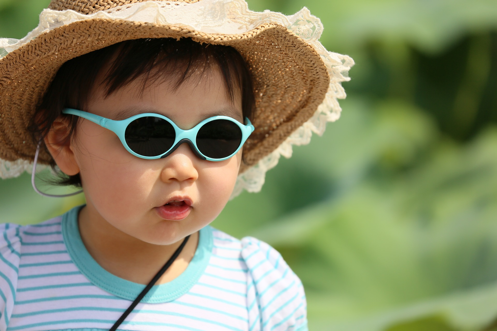 young child in protective sunglasses with wide brimmed hat